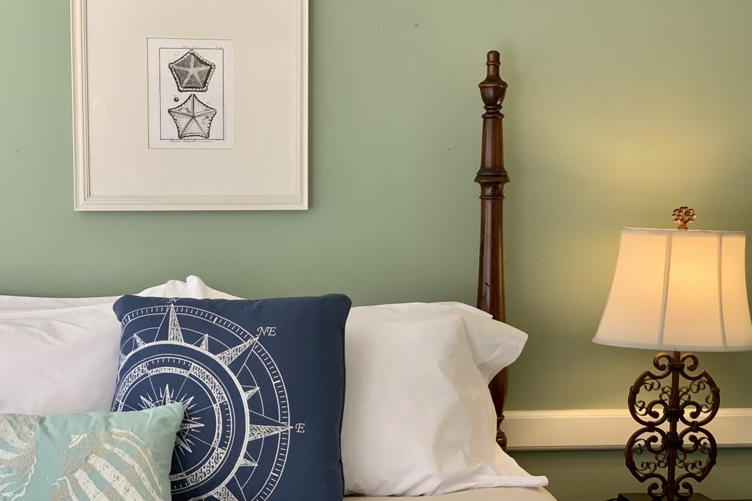 White poster bed with nautical pillow