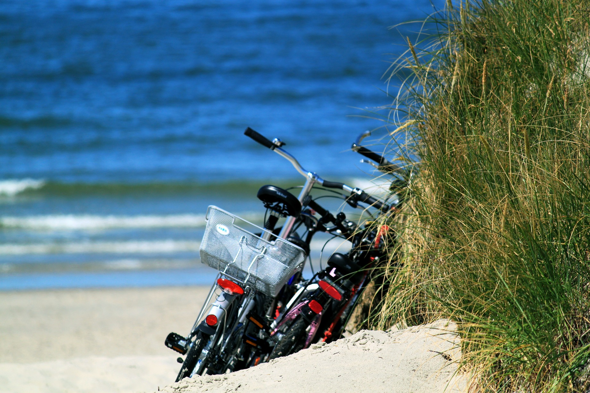 Bikes left by a dune on a beach on a sunny day with waves and beach grass